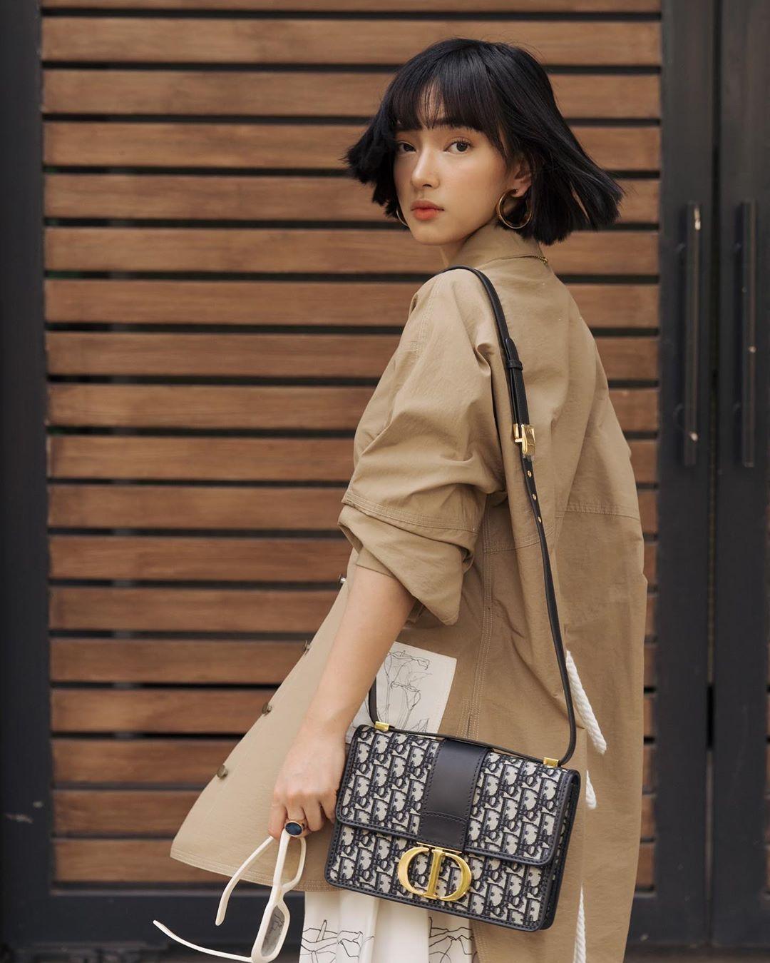 Châu Bùi mặc áo khoác be đeo túi Dior