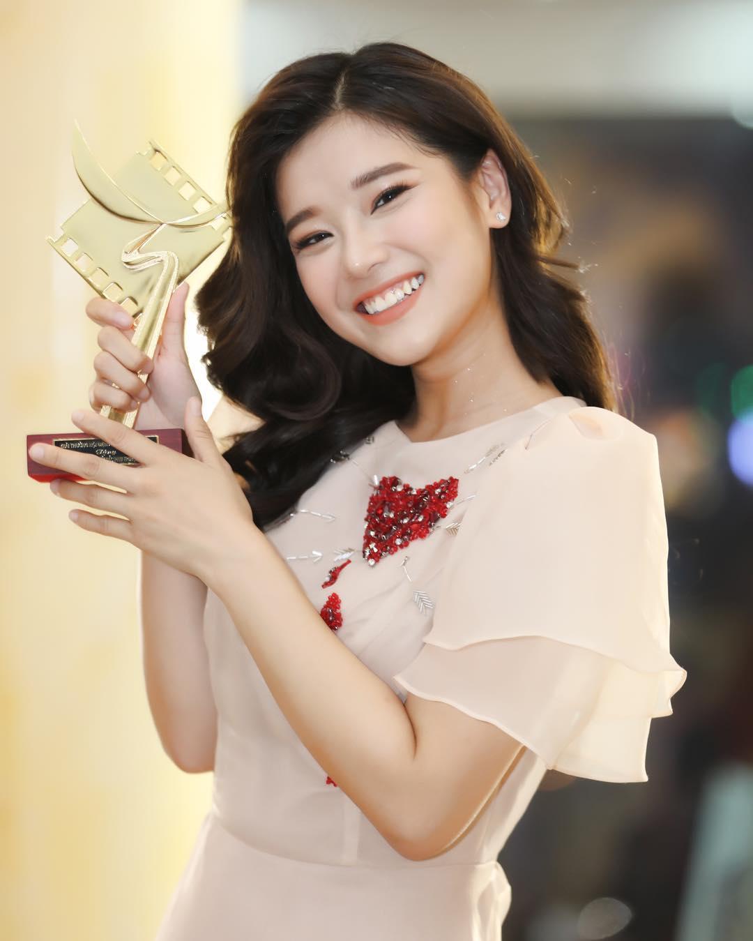 Hoàng Yến Chibi mặc váy trắng tay cầm cúp