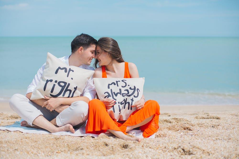 cặp đôi ôm gối trên bờ biển