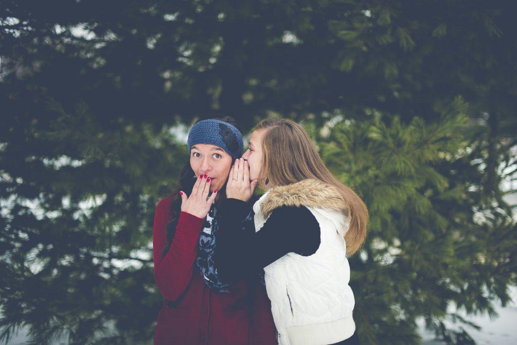hai cô gái đang thì thầm với nhau