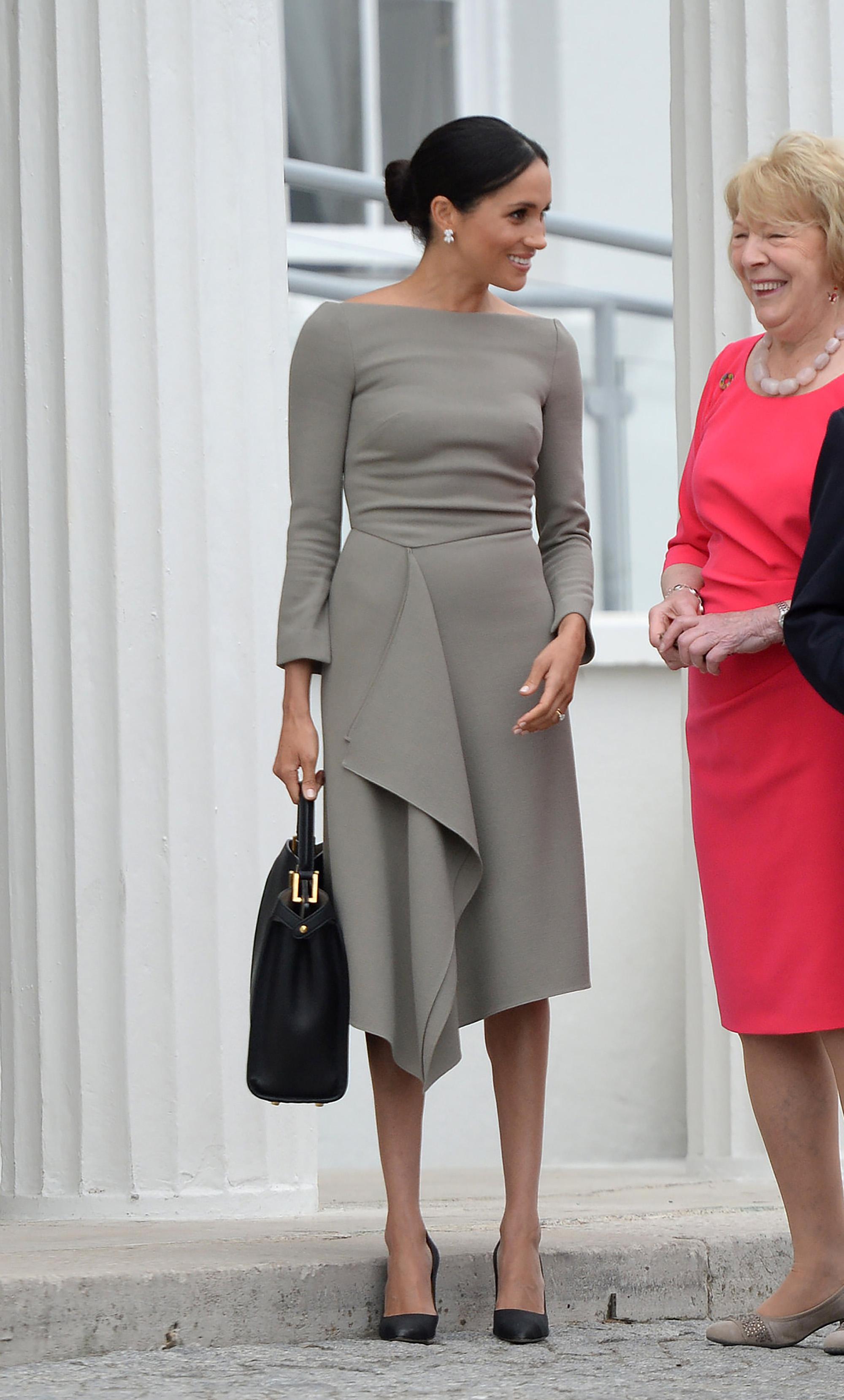 meghan mặc đầm màu xám và túi xách đen