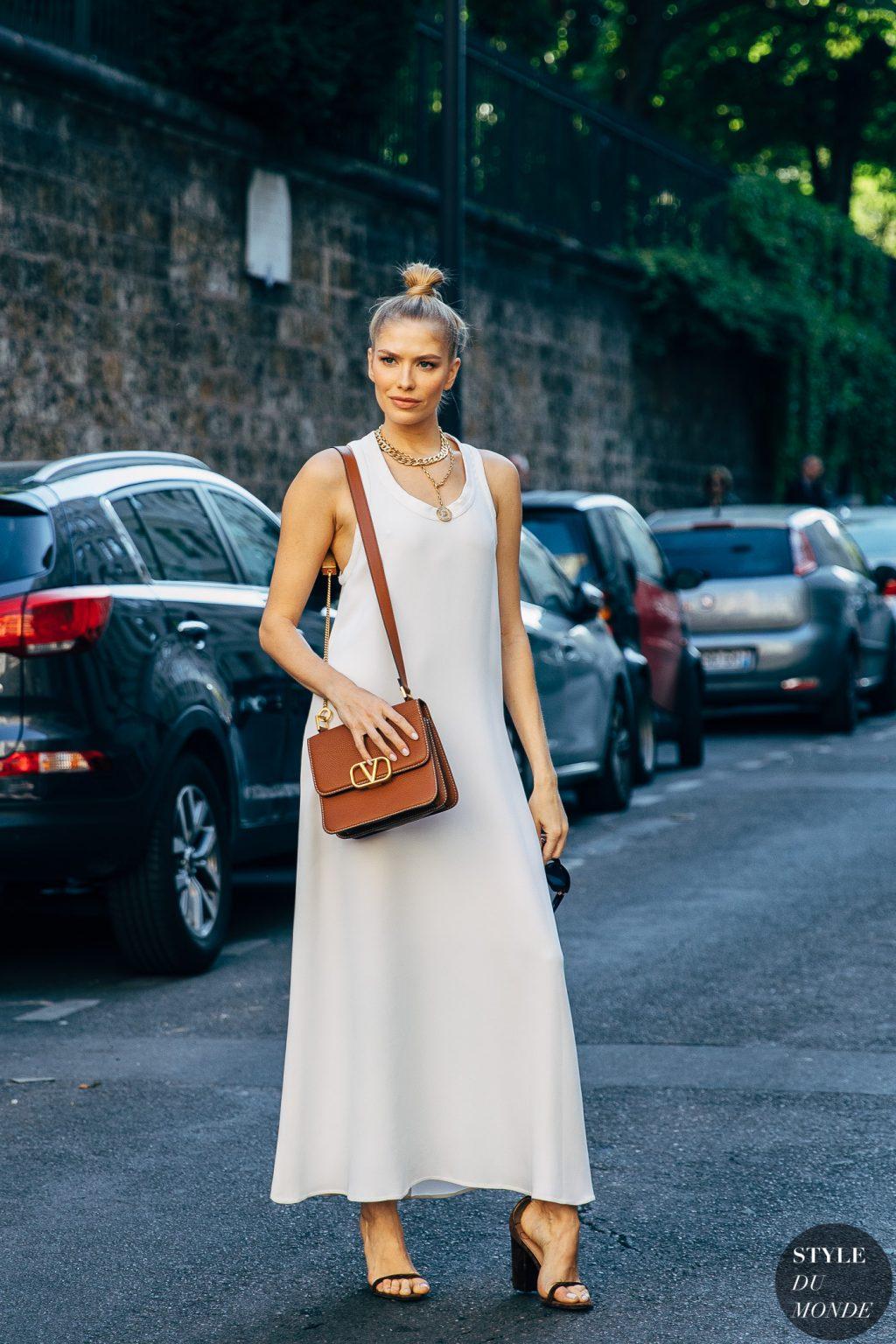 Fashionista mặc váy dài màu trắng mang túi nâu