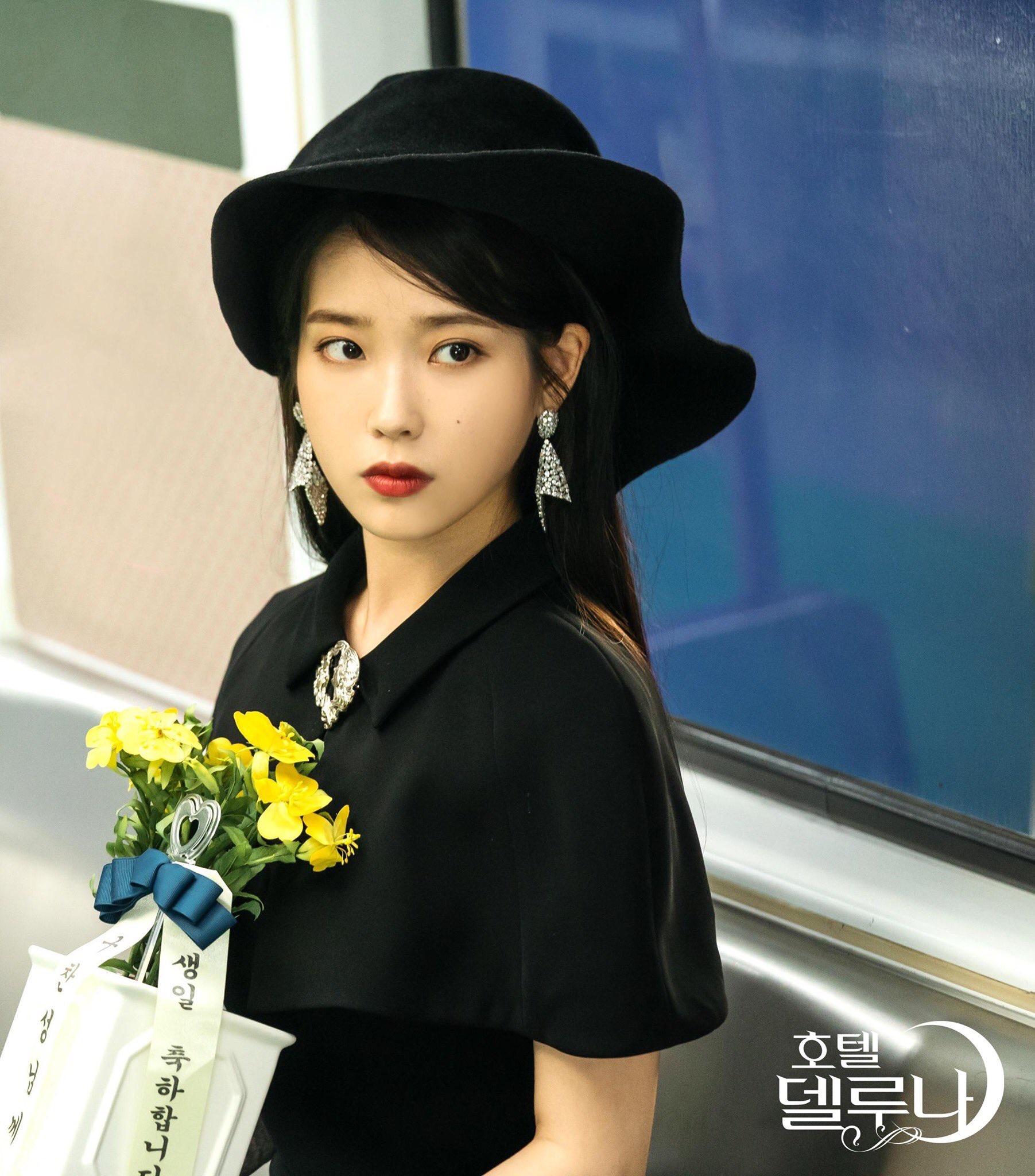 iu đầm đen mũ đen hoa vàng