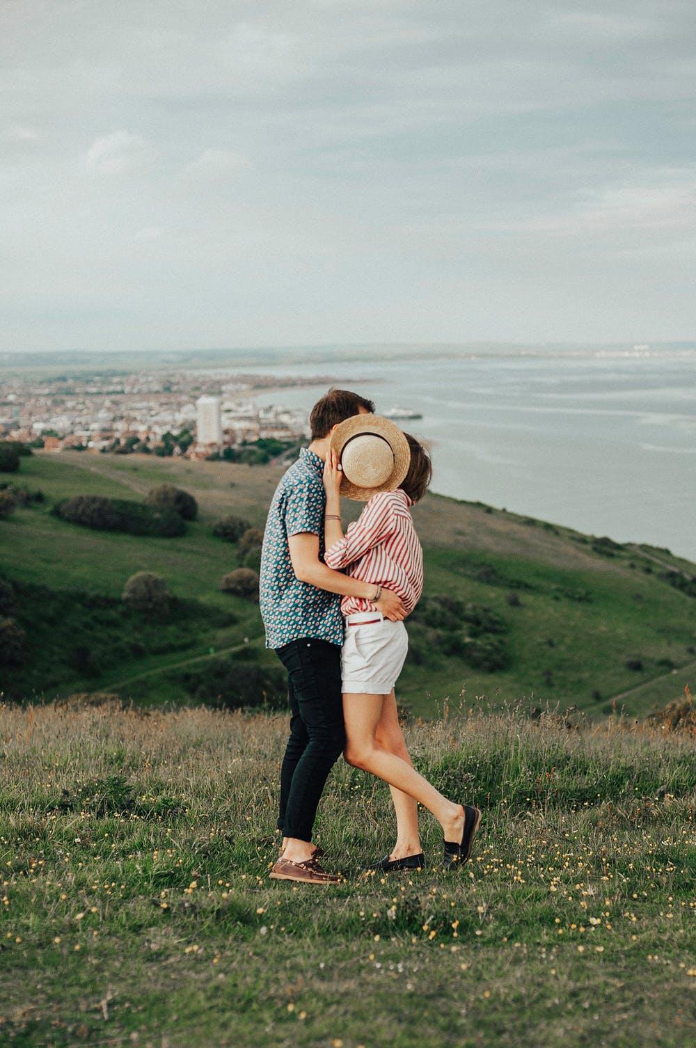 cặp đôi ôm nhau lấy nón che mặt