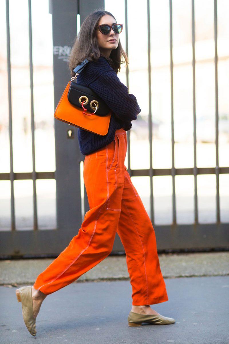 fashionista mặc quần ống rộng màu cam và áo đen