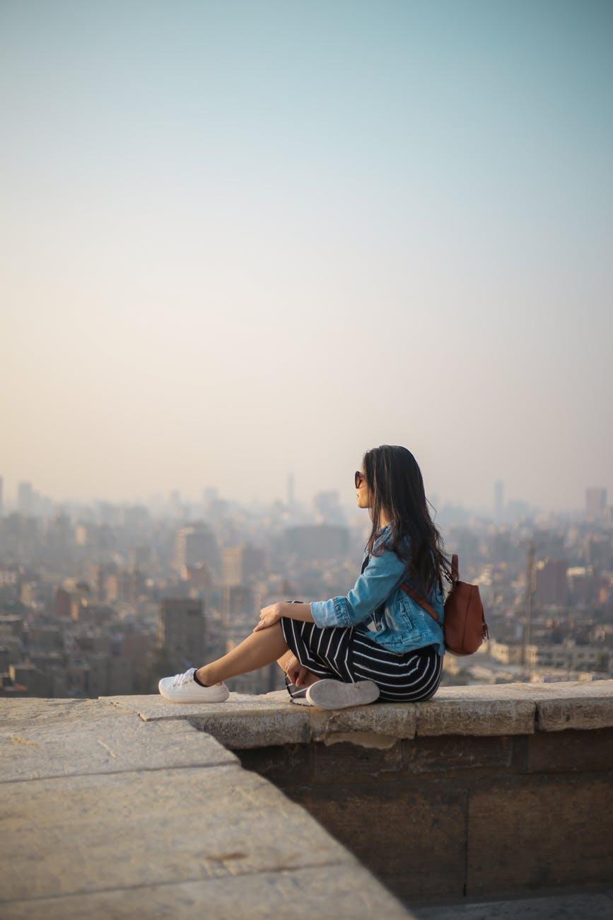 cô gái ngồi ngắm thành phố