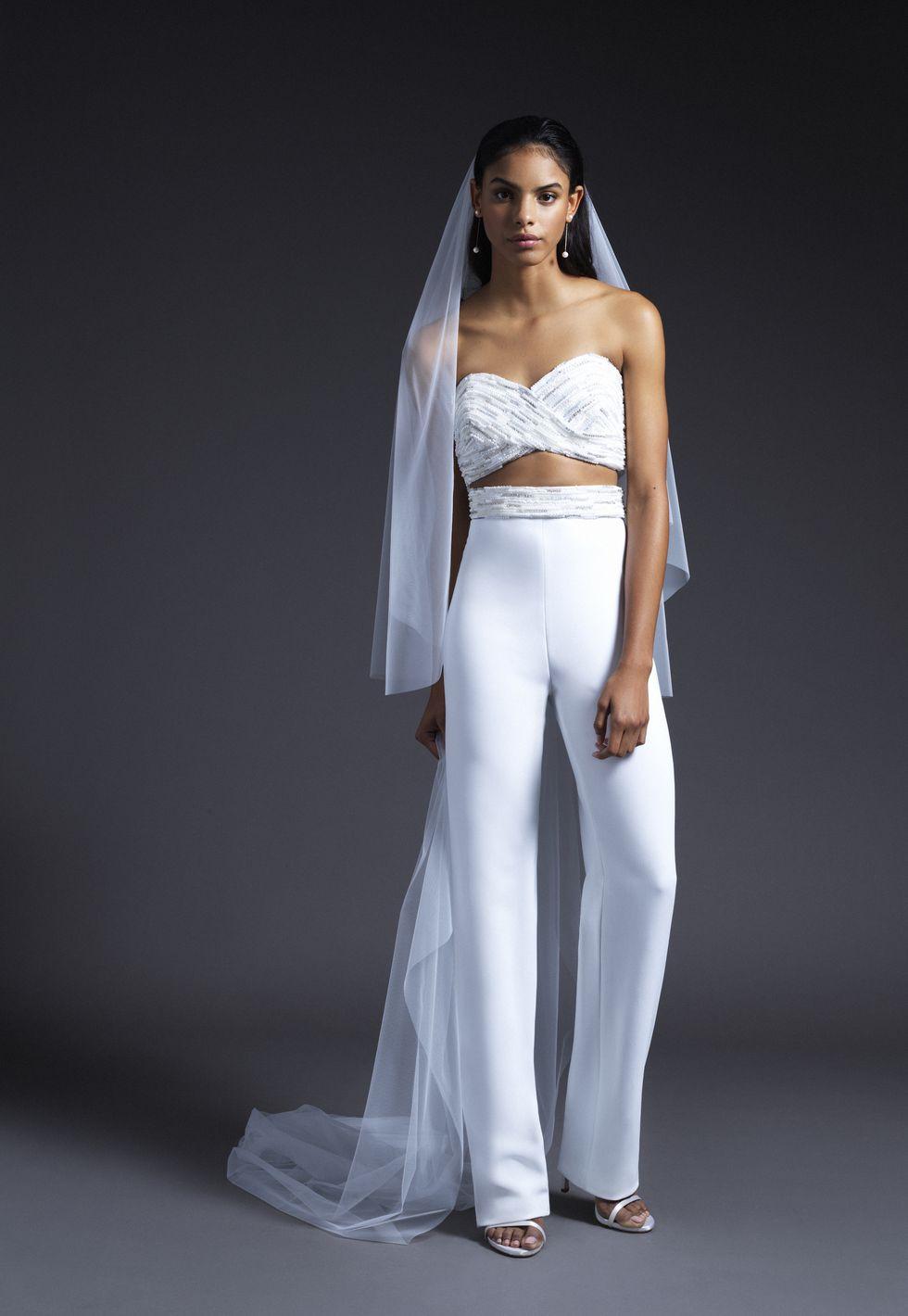 Trang phục cưới với kiểu dáng mới lạ trong bộ sưu tập mùa Thu 2019 của thương hiệu Cushnie. Thiết kế kết hợp áo crop top và quần lưng cao ống suôn mang đến vẻ đẹp cá tính cho trang phục.