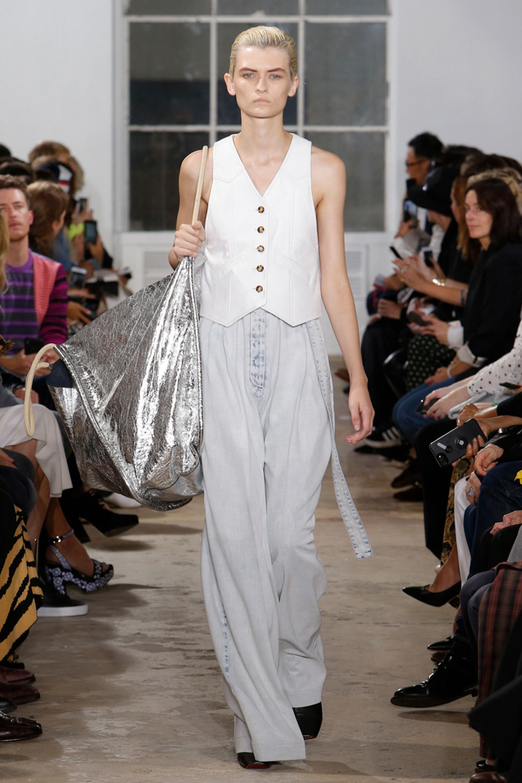 Người mẫu mặc áo trắng mang túi xách to màu bạc Proenza Schouler