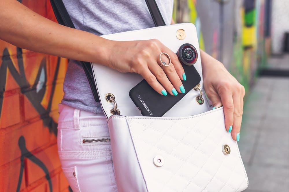 cô gái bỏ điện thoại vào túi xách