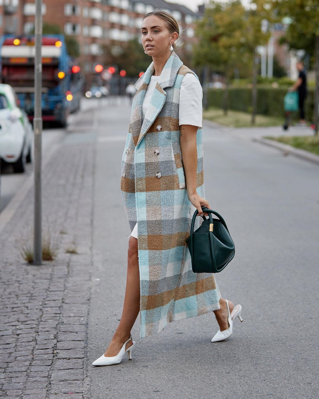 Fashionista mặc áo khoác kẻ ô vuông đi giày cao gót trắng
