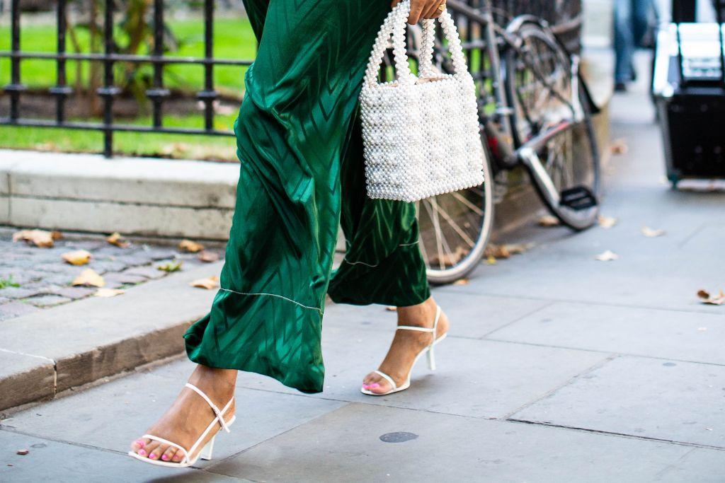 Fashionista mặc quần dài màu xanh lá cây đi giày sandals trắng
