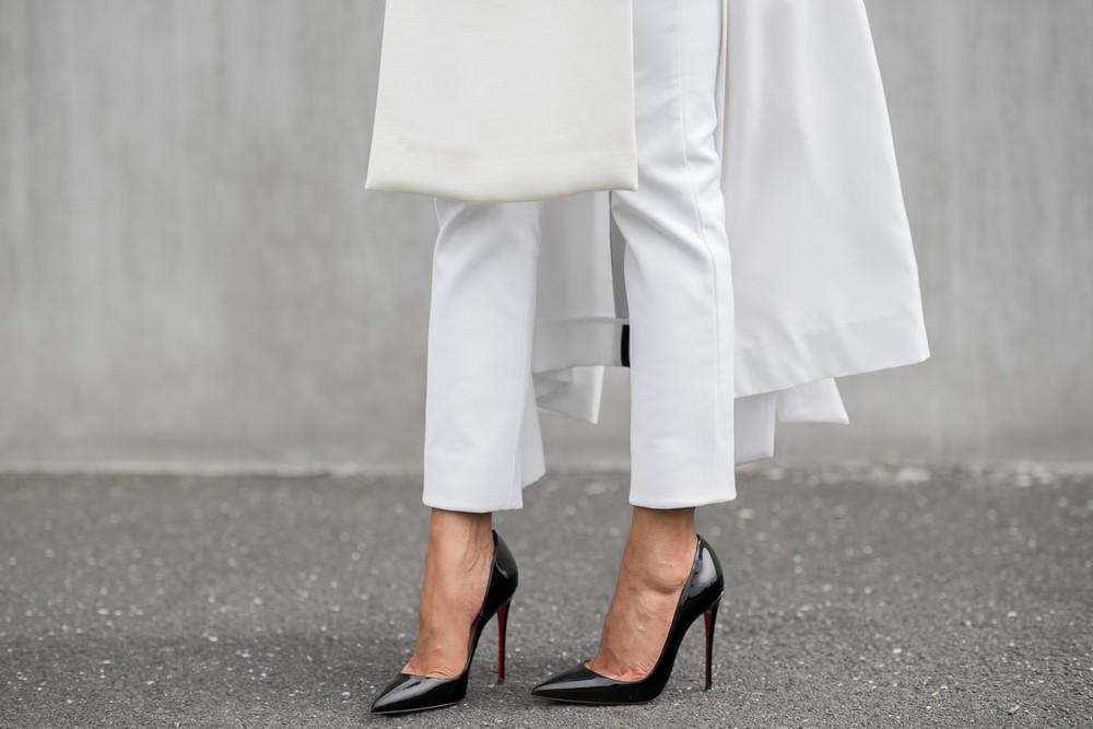 Fashionista mặc quần trắng đi giày cao gót đen