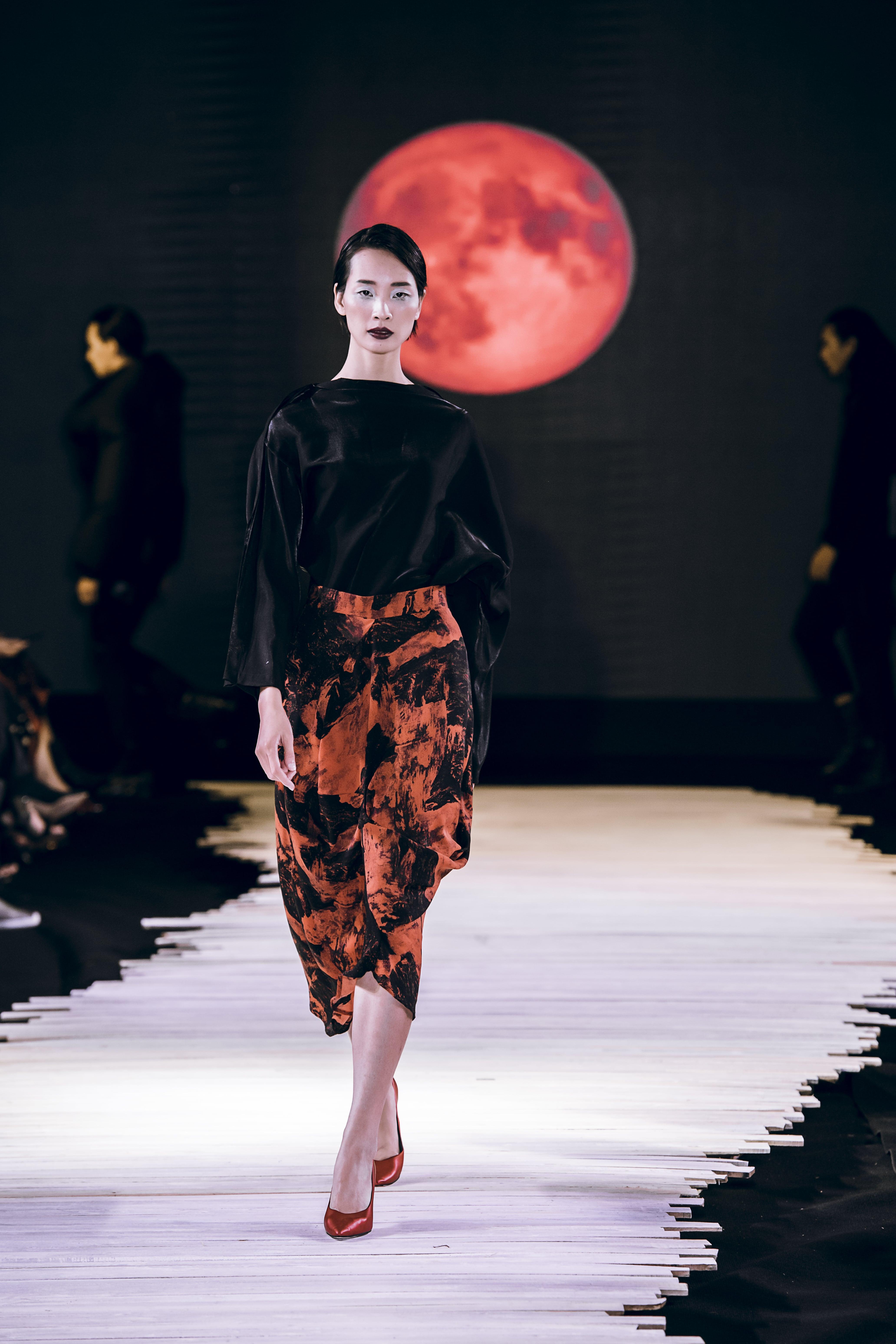 Người mẫu mặc áo đen và chân váy đỏ sẫm màu