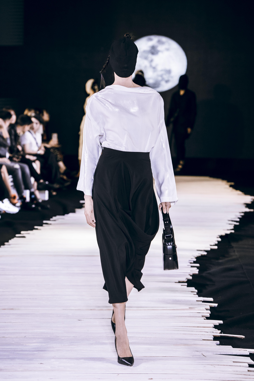 Người mẫu mặc áo trắng chân váy đen