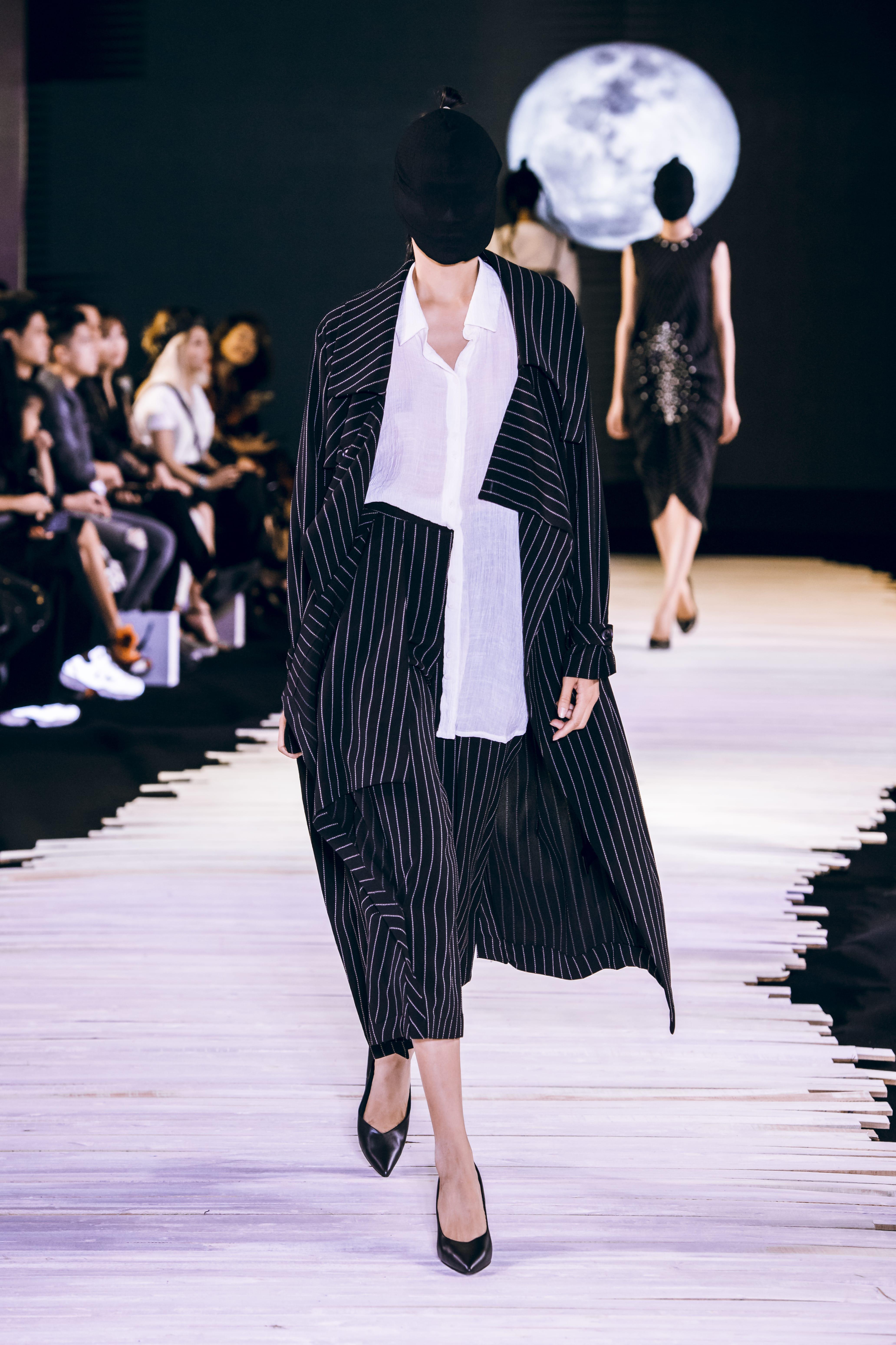Người mẫu mặc áo trắng và áo khoác kẻ sọc đen