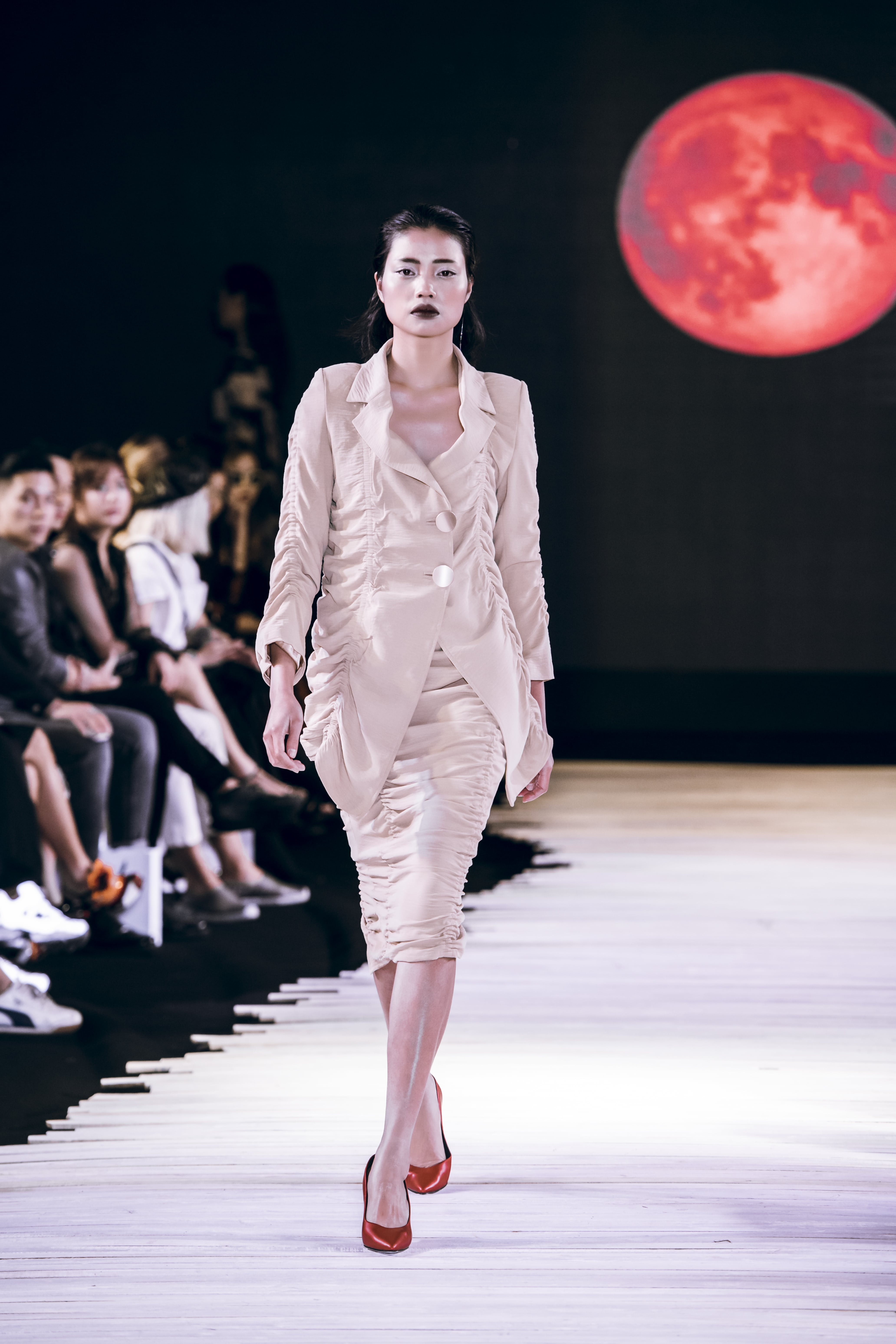 Người mẫu mặc áo vest và chân váy trắng