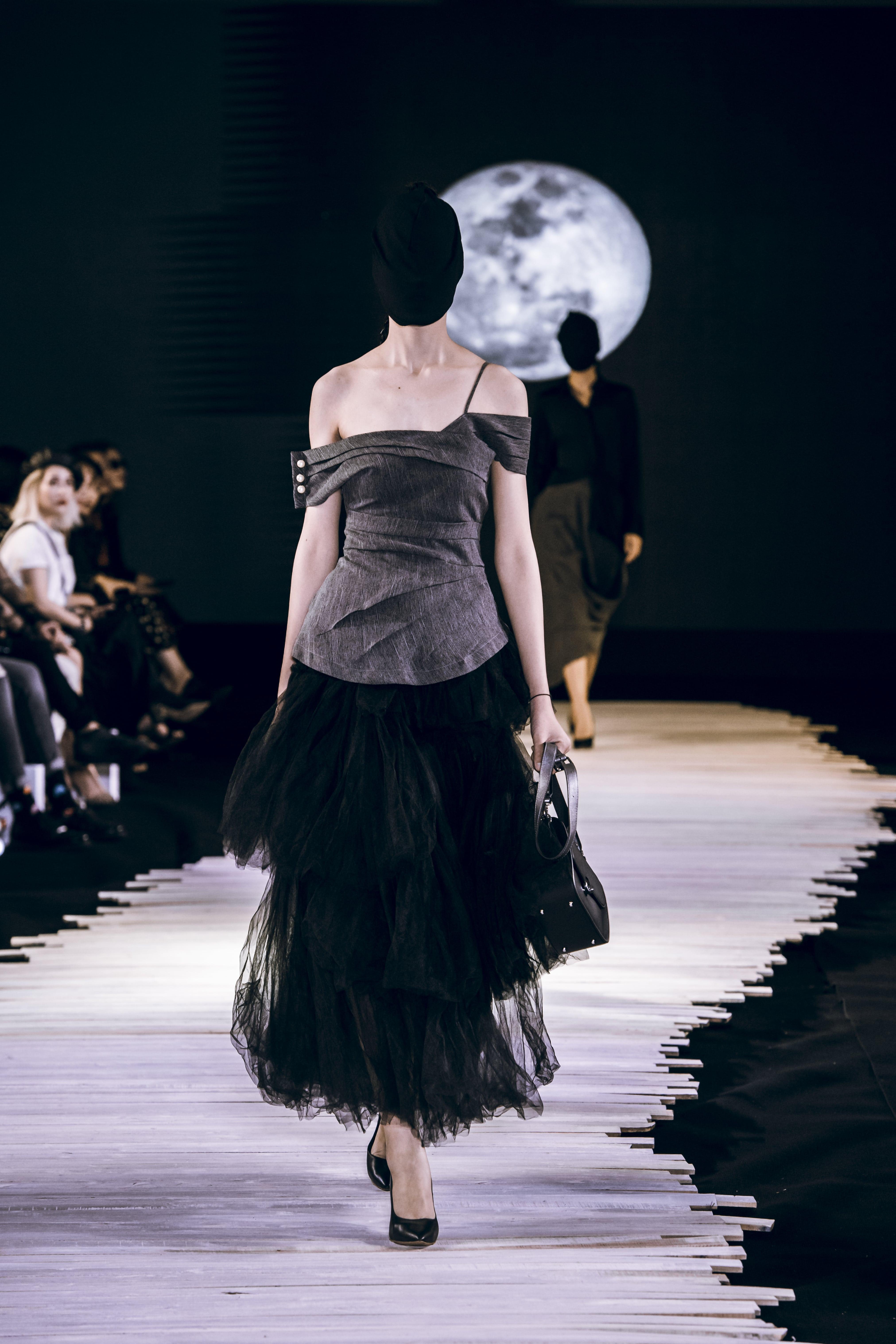 Người mẫu mặc áo xám lệch vai và chân váy đen