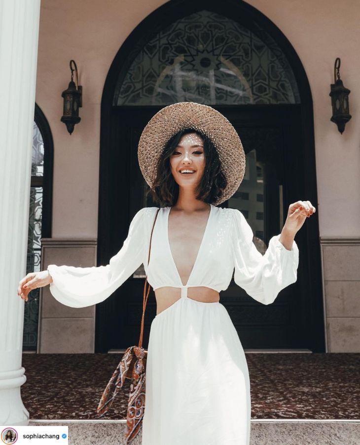 sophia chang mặc đầm trắng tay dài khoét eo nón cói rộng vành