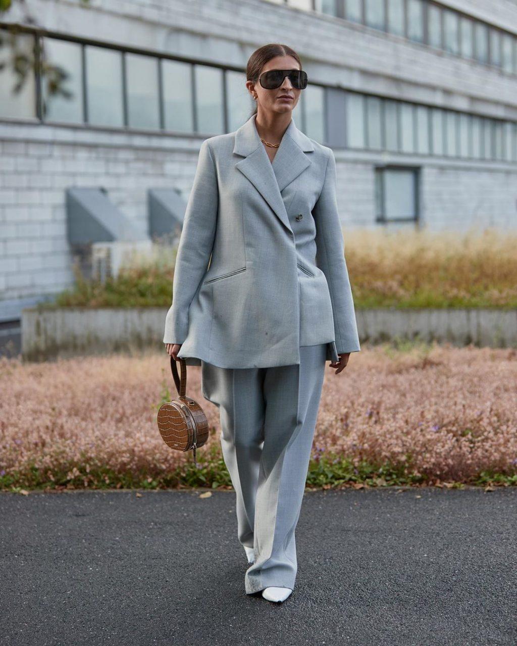 Fashionista mặc quần âu và áo blazer màu xanh cầm túi giả da cá sấu