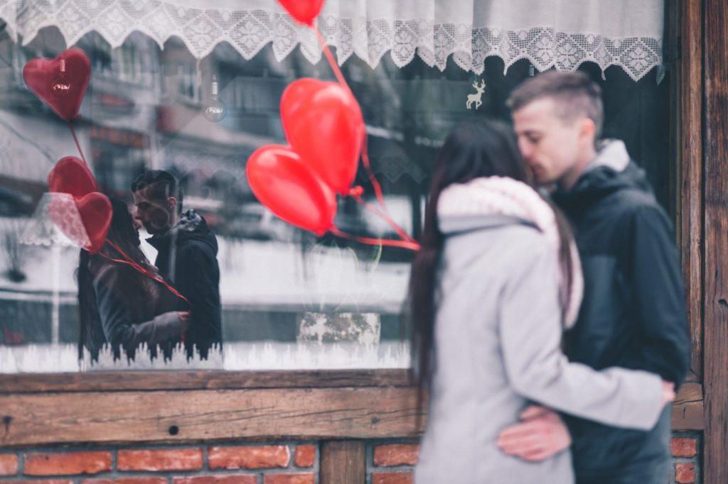 cặp đôi ôm nhau cầm bóng bay