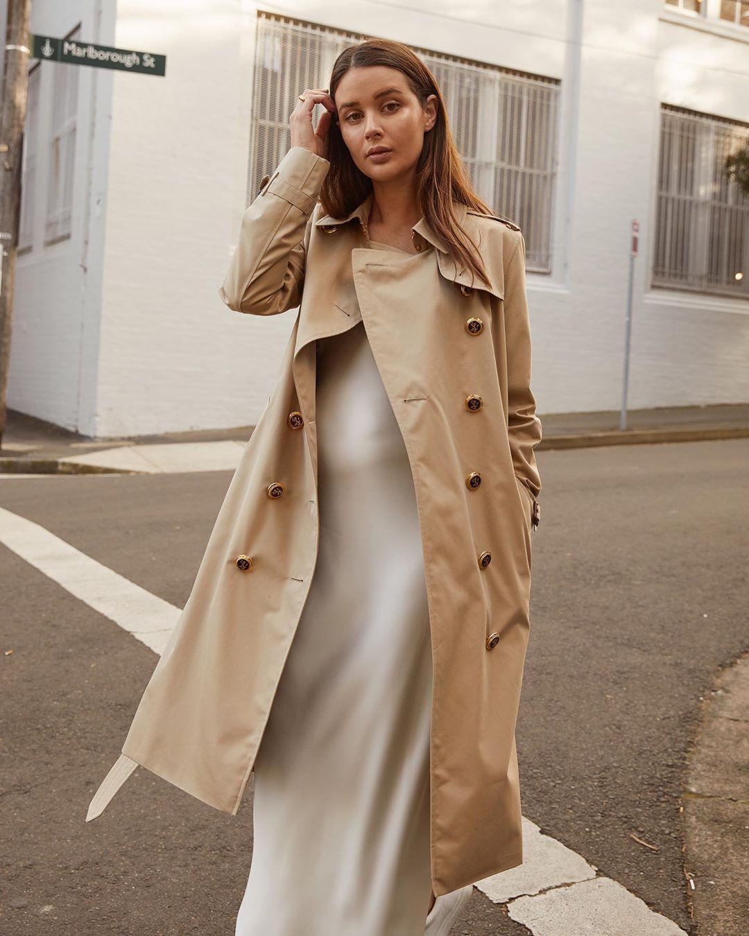sara crampton mặc áo trench coat và đầm trắng
