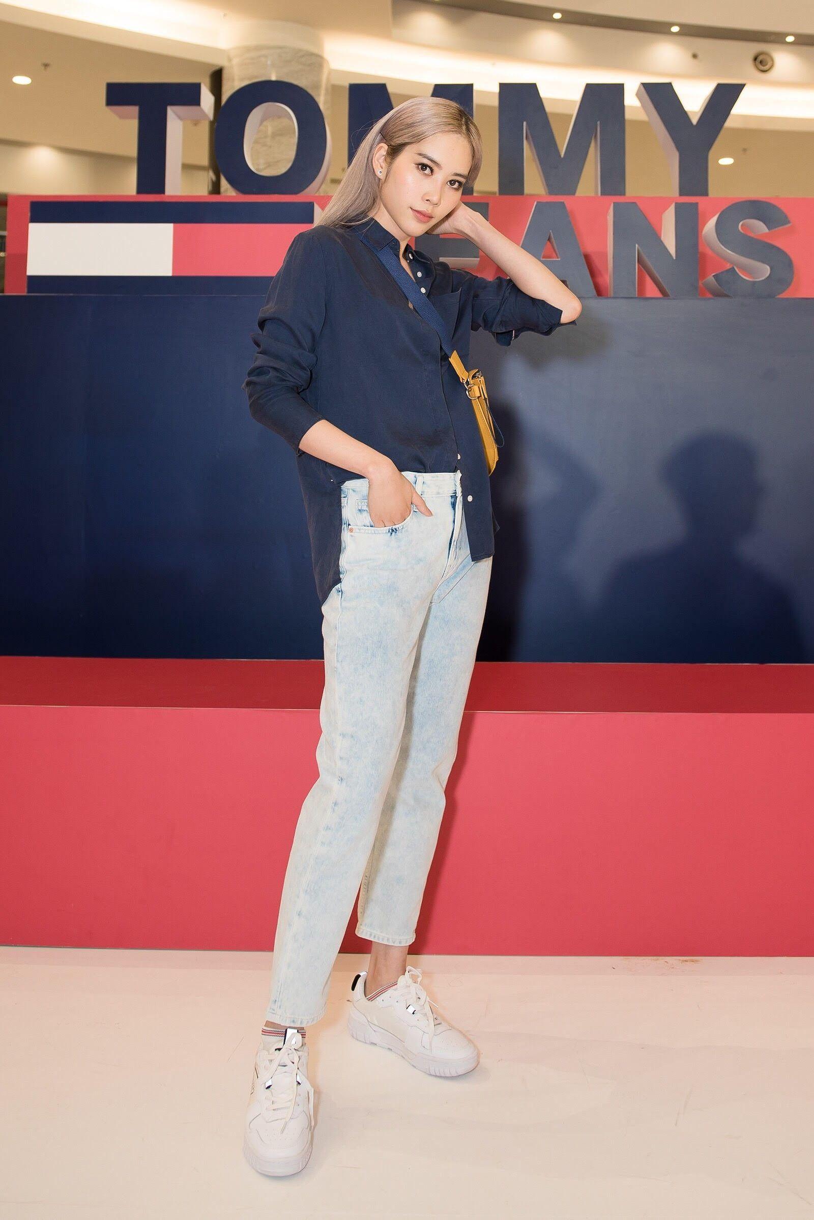 Hoa hậu Nam Em với phong cách trẻ trung năng động với gồm áo sơ mi, quần jeans, túi đeo chéo và giày sneaker.