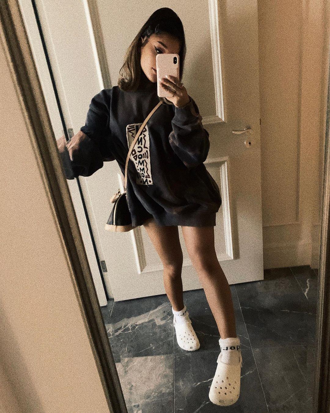 """Ngày 10/9 vừa qua, cô ca sĩ Ariana Grande đã đăng ảnh selfie trong bộ trang phục """"đậm chất"""" VSCO girl lên Instagram. Trong hình, cô diện áo oversize và đặc biệt là giày Crocs cùng vớ."""