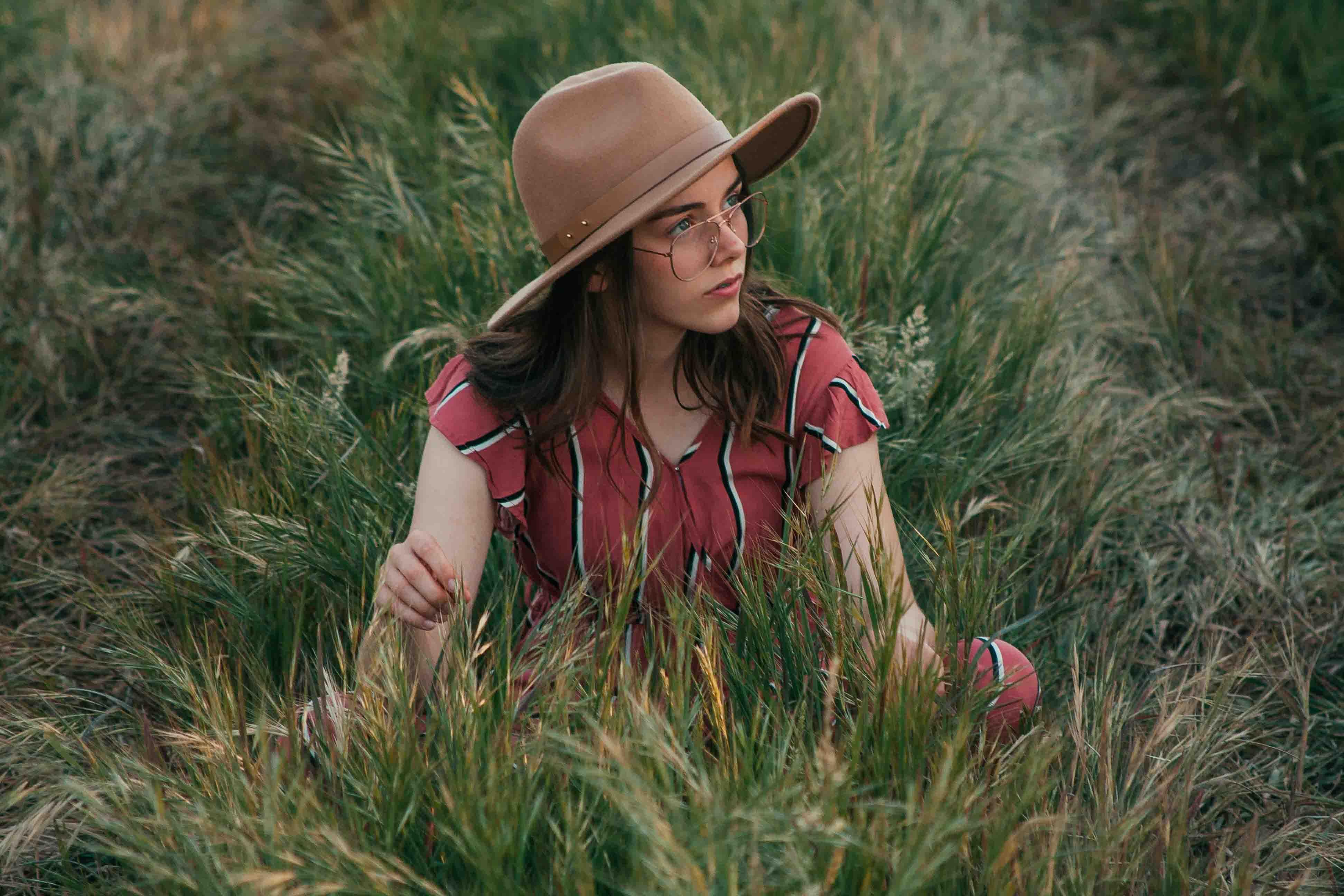 cô gái ngồi giữa đồng cỏ