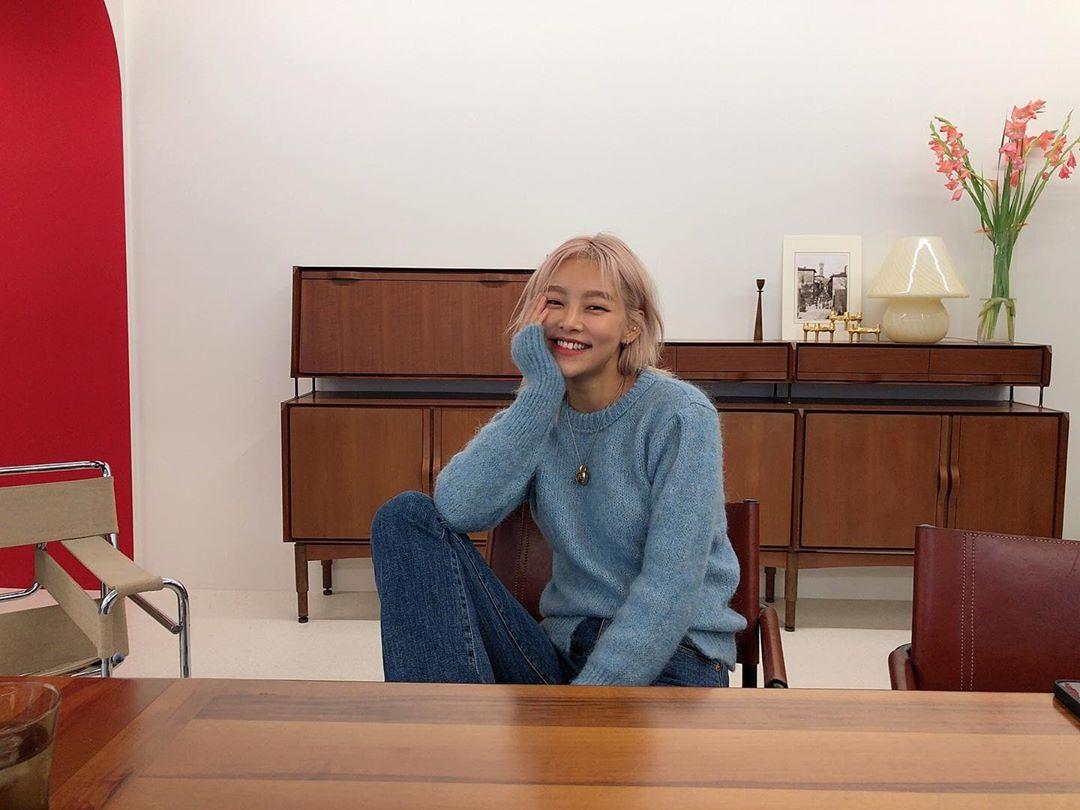 hong haena mặc áo len xanh và quần jeans