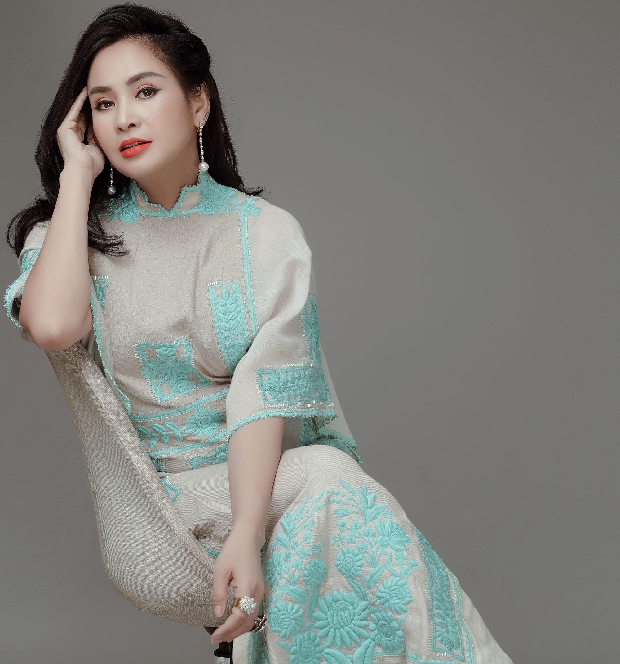 phụ nữ Thanh Lam mặc đầm xanh ngồi trên ghế
