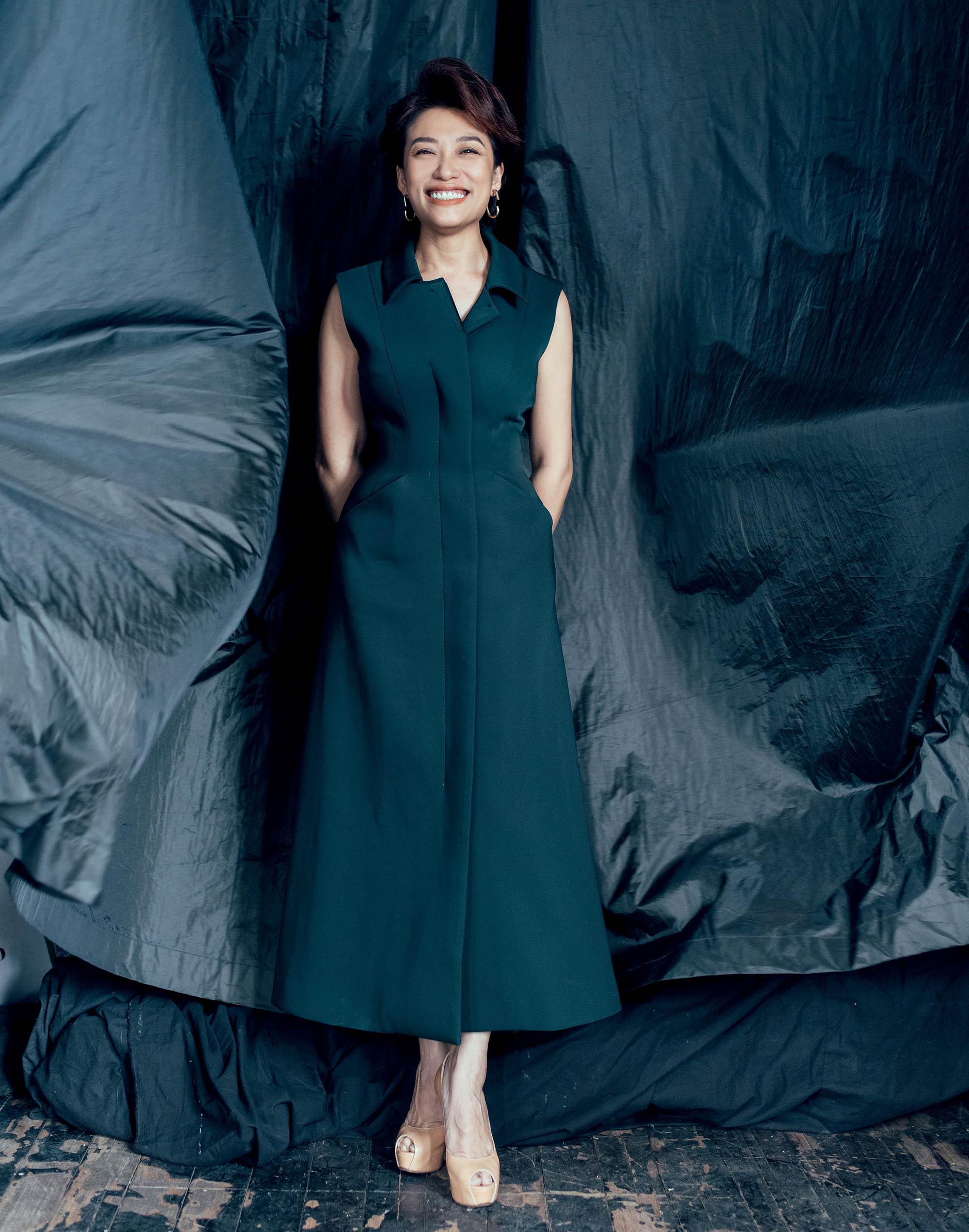 Trần Ly Ly đứng thẳng mặc đầm xanh