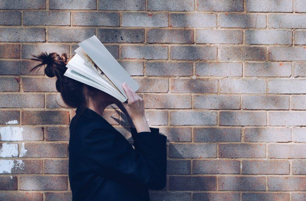 cô gái dùng sách che mặt