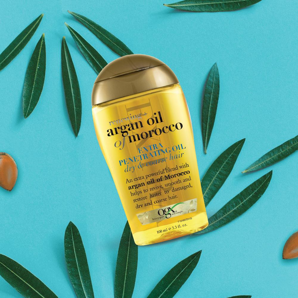 hair oil ogx argan oil morocco trên nền xanh biển có lá cây