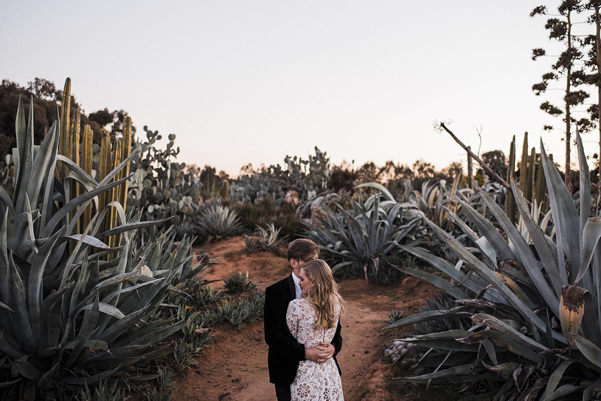 cặp đôi đứng giữa vườn xương rồng