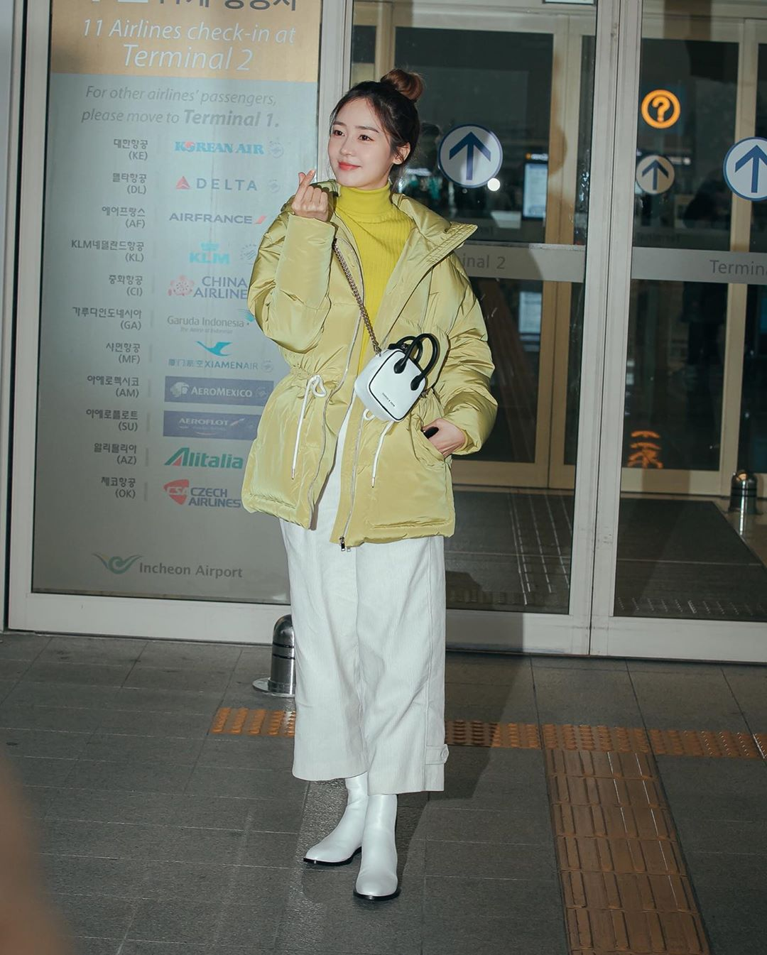 Sung Yuri áo cổ lọ màu vàng chanh và boots trắng