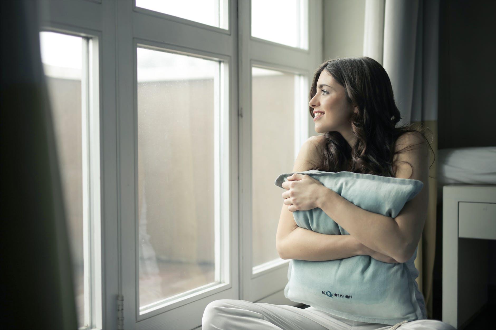 cô gái ôm gối mỉm cười