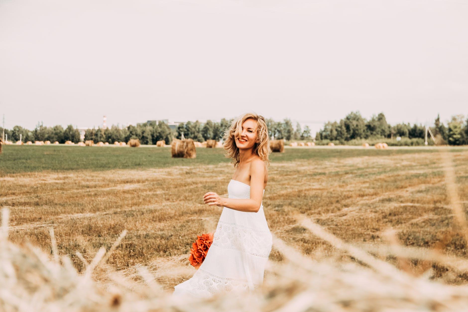 cô gái váy trắng cầm bó hoa