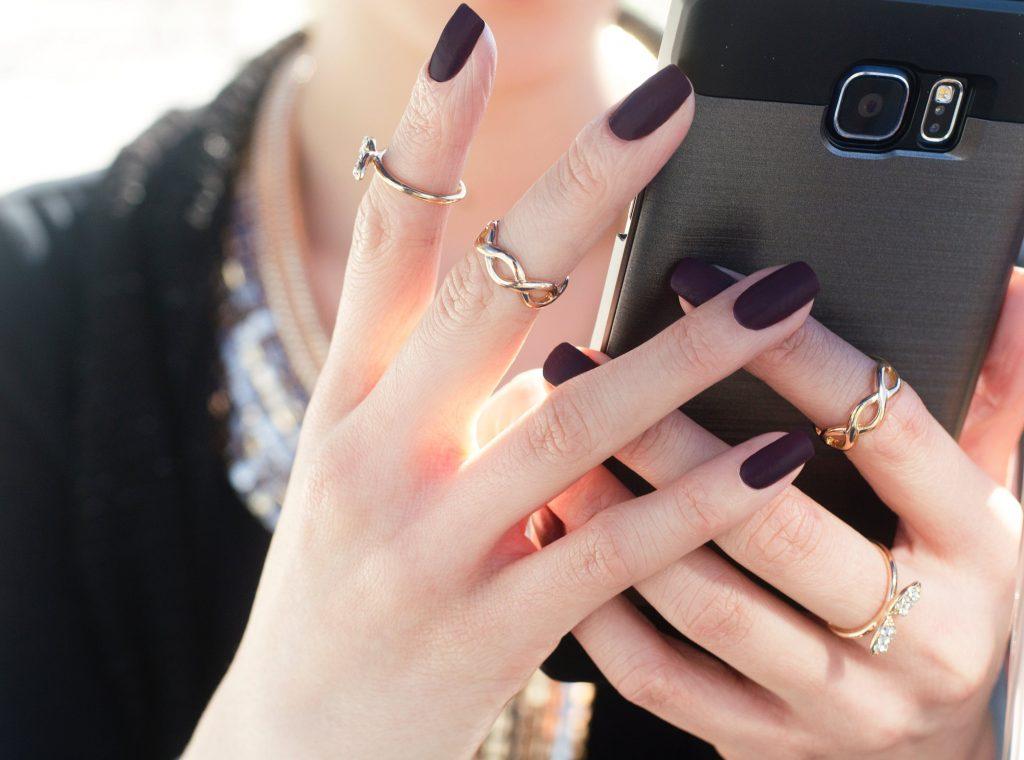 Móng tay đẹp-Bàn tay cầm điện thoại.