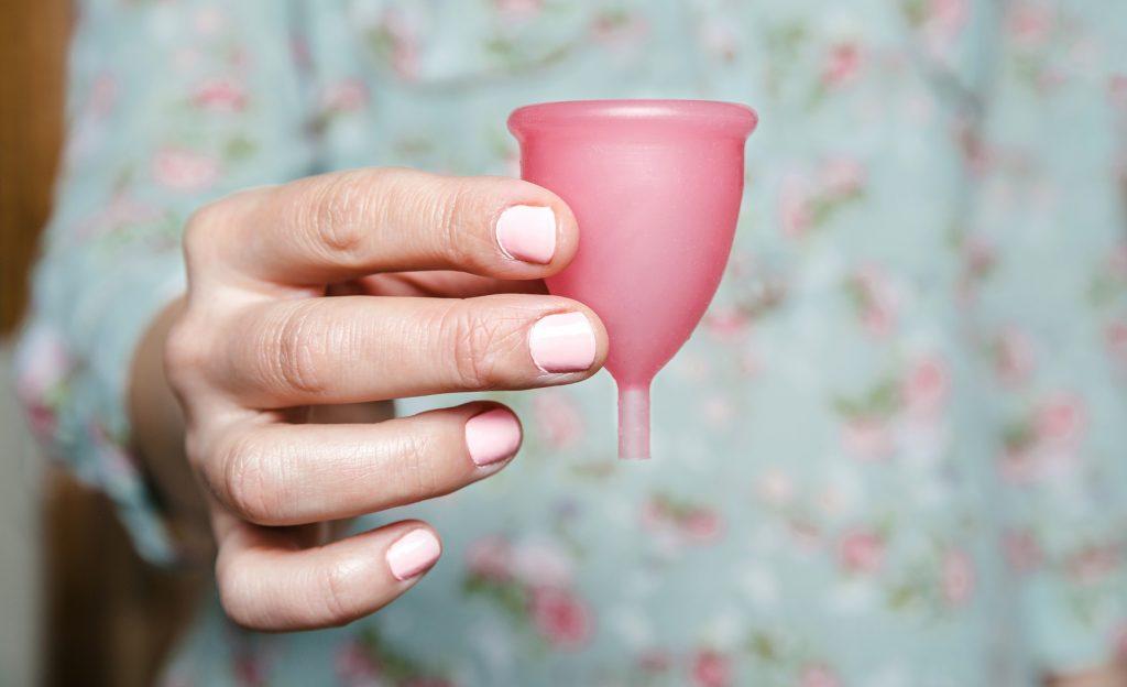 Cốc nguyệt san-Bàn tay cầm cốc màu hồng.