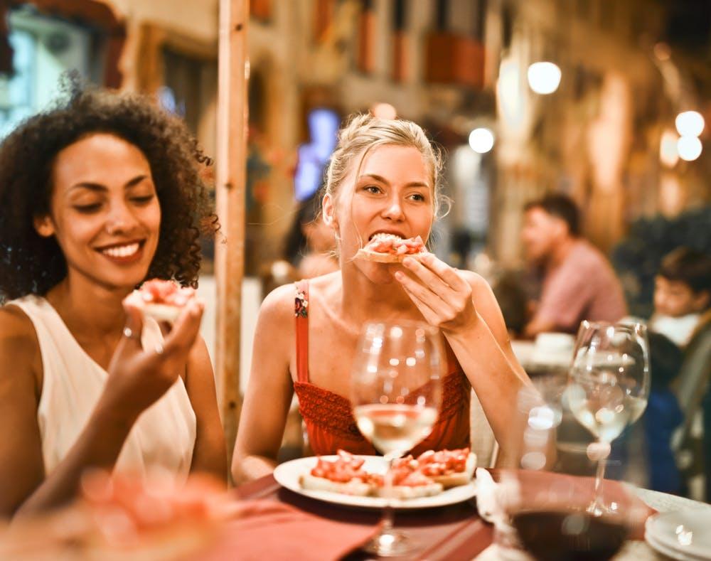Thói quen ăn uống-Hai cô gái đang ăn pizza.