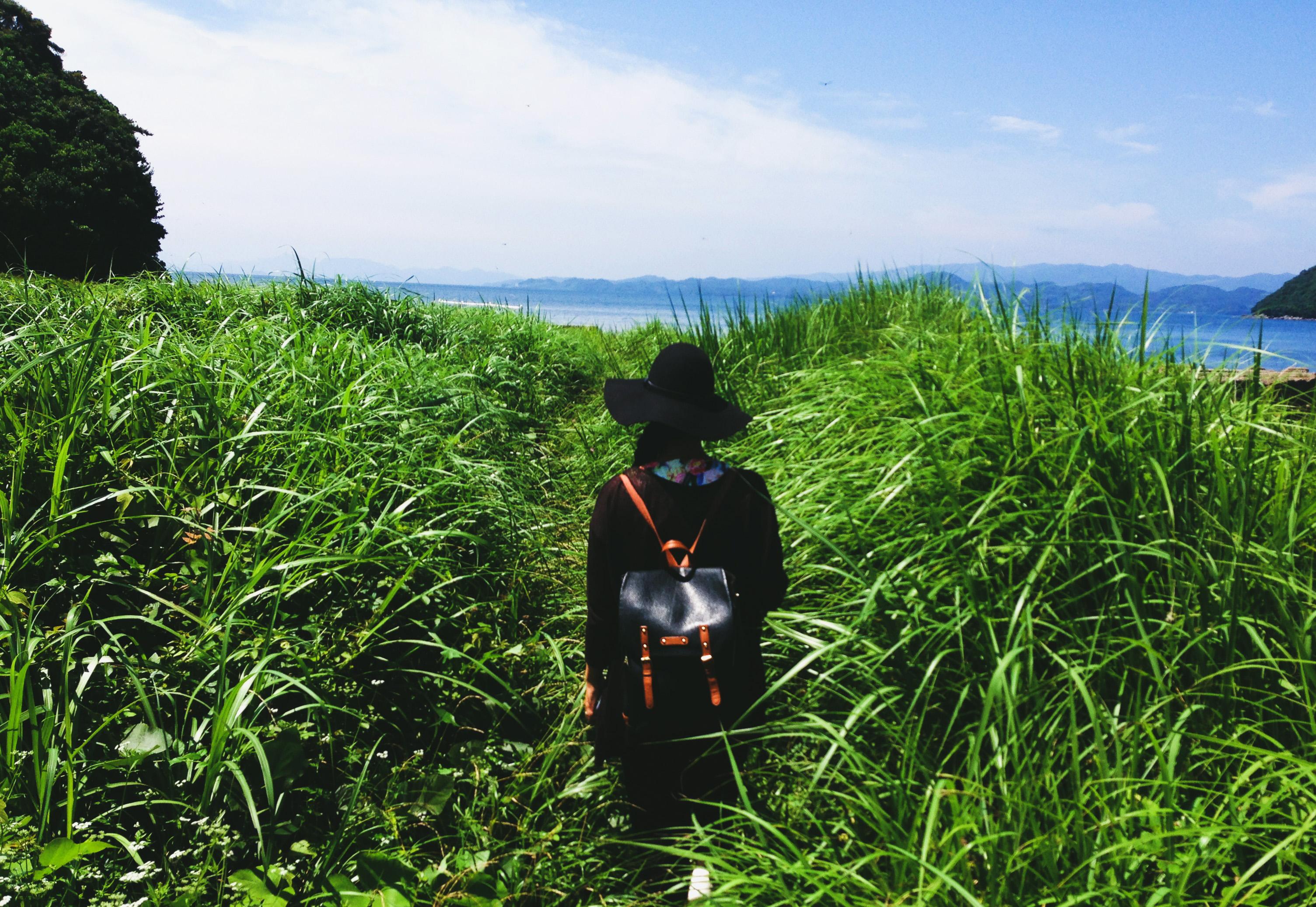 cô gái mang balo trên đồng cỏ