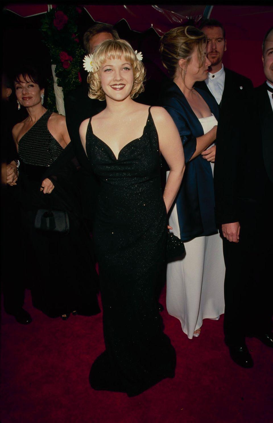 Drew Barrymore mặc đầm dạ hội đen và cài hoa lên tóc trên thảm đỏ Oscar năm 1998