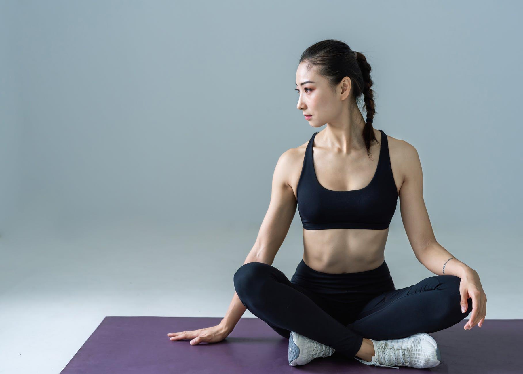 Sai lầm khi tập gym-Cô gái ngồi trên thảm tập.