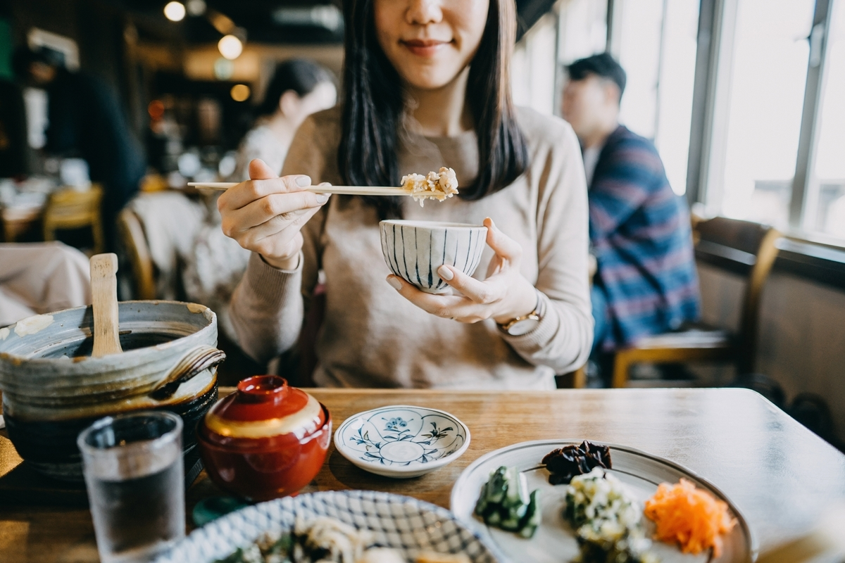 Chế độ ăn kiêng giảm cân-Cô gái đang gắp đồ ăn.