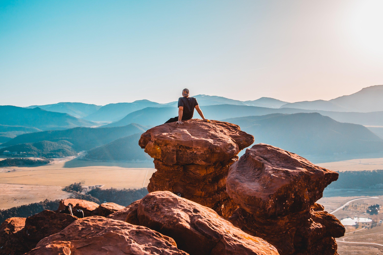 chàng trai ngồi trên núi