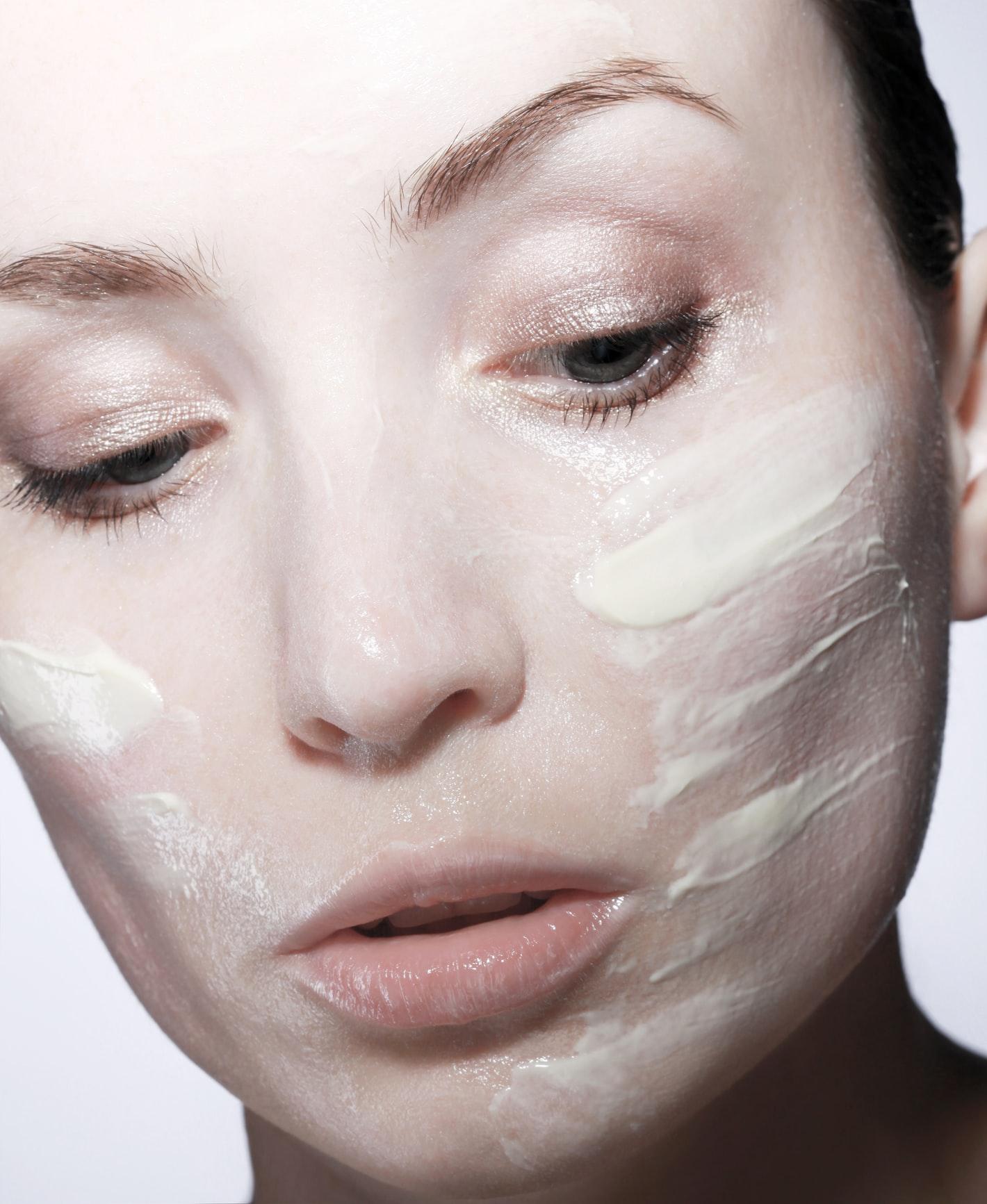 Cách dùng retinol-Cô gái bôi kem lên da.