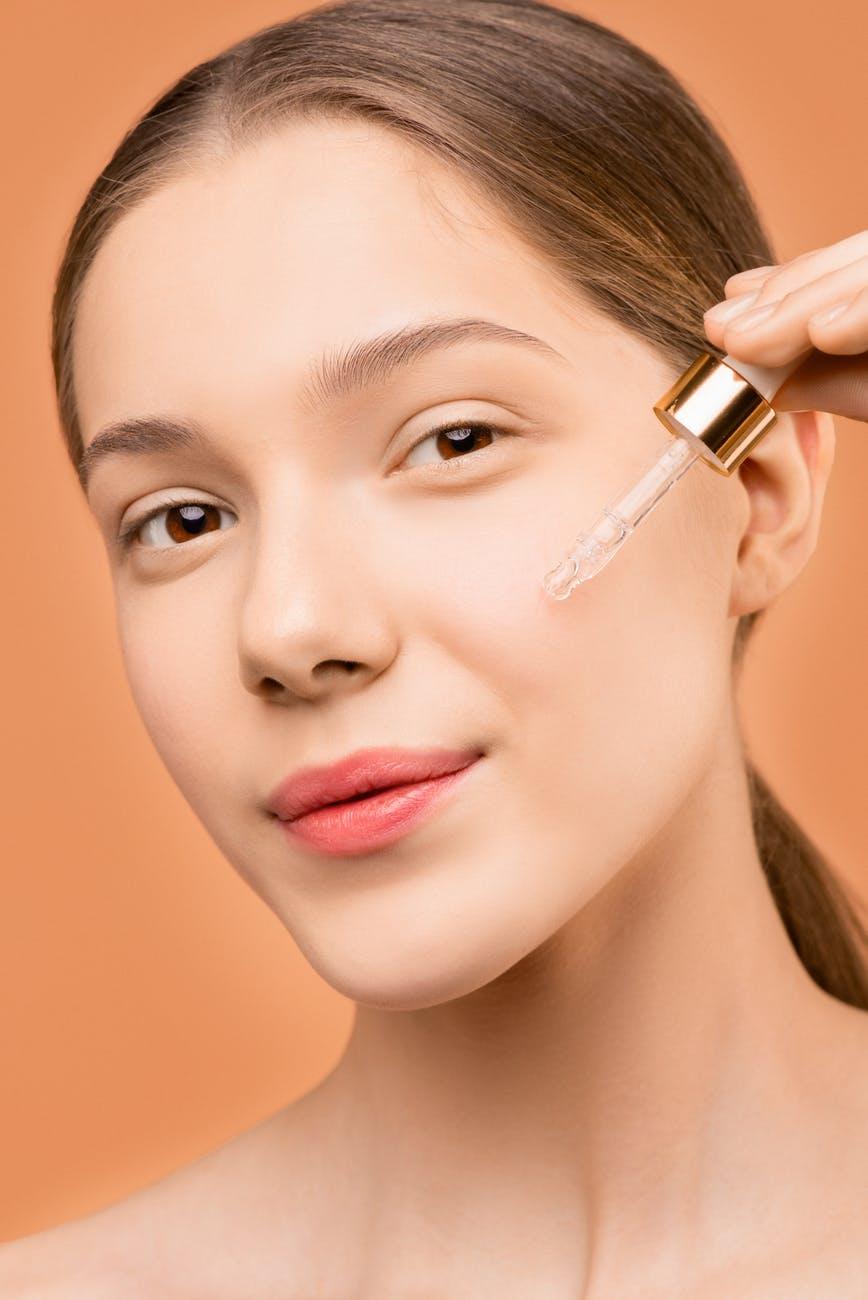 Cách dùng retinol-Cô gái nhỏ serum lên mặt.