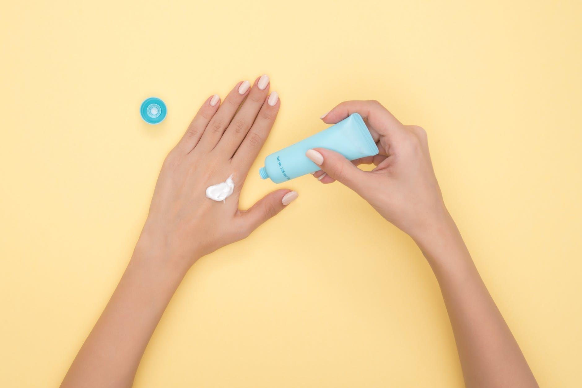 Kem chống nắng-Bàn tay cầm tuýp kem màu xanh.