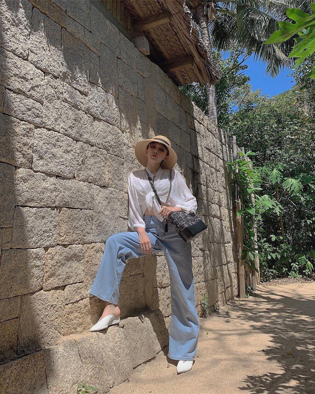 Tóc Tiên diện quần jeans phom rộng trẻ trung cùng sơ mi trắng và mũ rộng vành