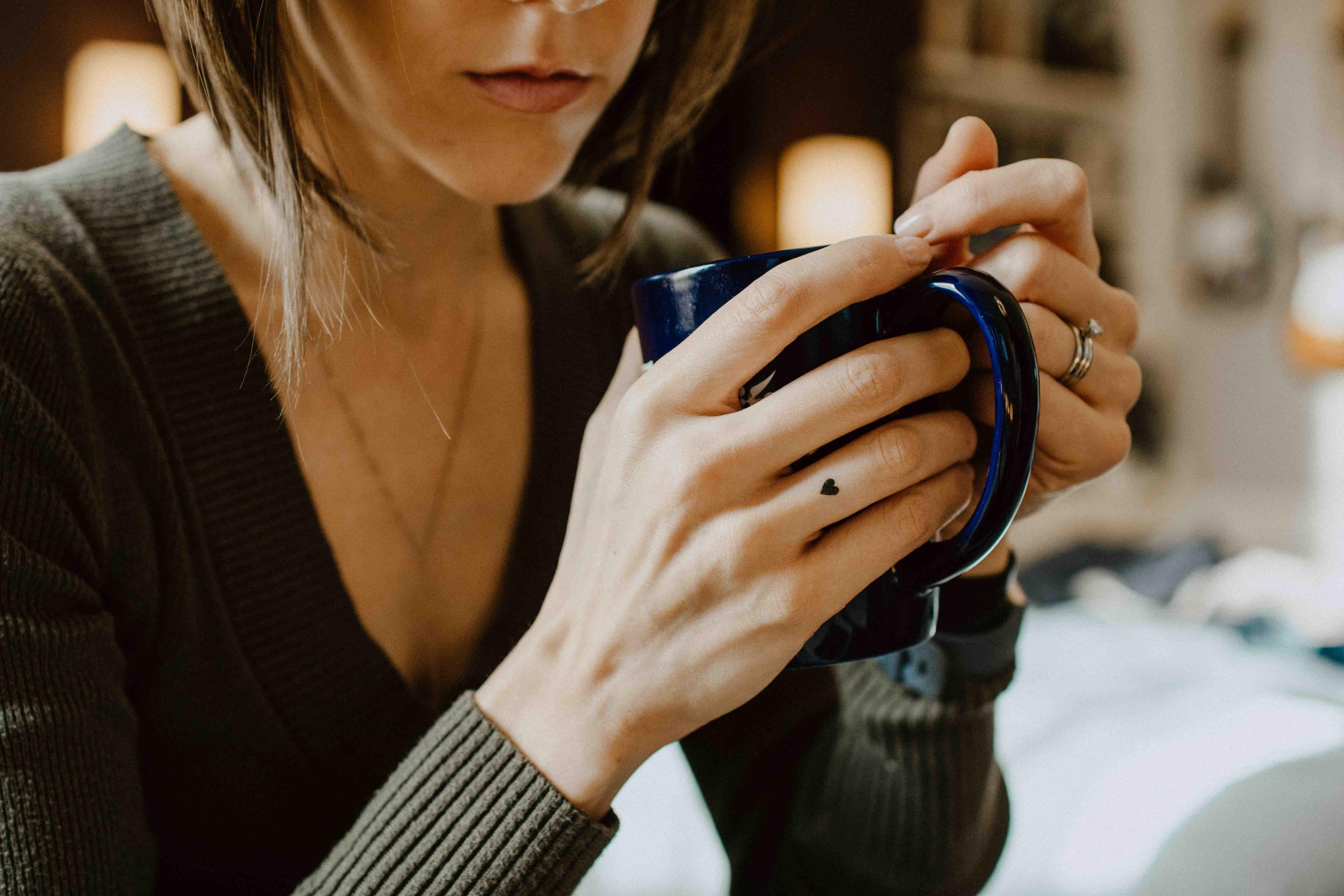 người phụ nữ cầm ly cà phê